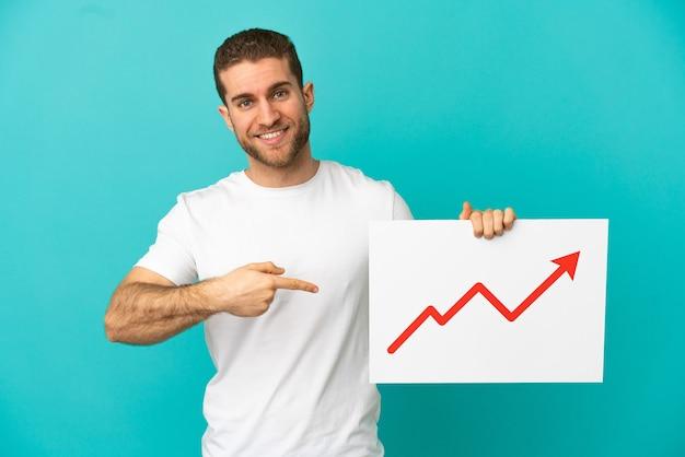 성장 통계 화살표 기호로 기호를 누르고 그것을 가리키는 격리 된 파란색 배경 위에 잘 생긴 금발의 남자