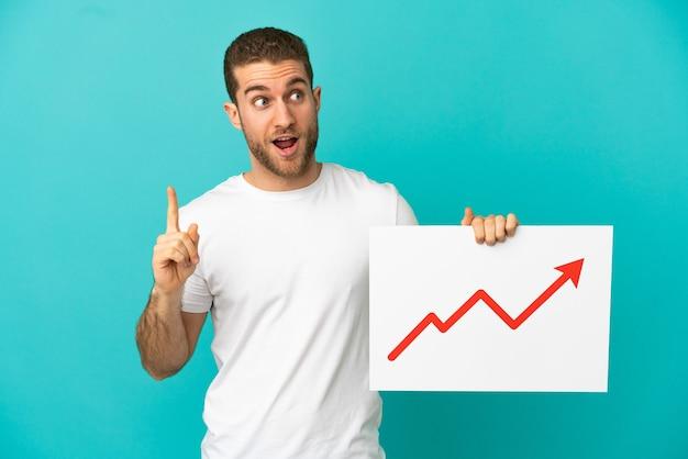 成長している統計矢印記号と思考のサインを保持している孤立した青い背景の上のハンサムなブロンドの男