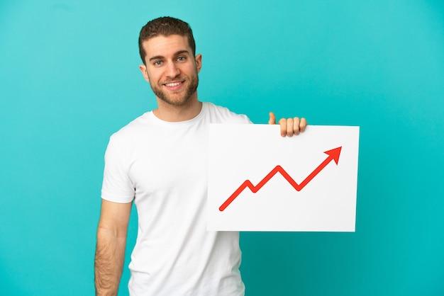 幸せな表情で成長している統計矢印記号で看板を持っている孤立した青い背景上のハンサムな金髪の男