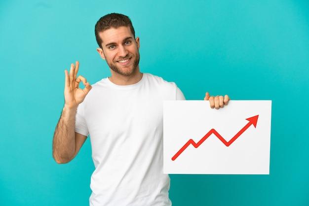 孤立した青い背景上のハンサムな金髪の男は、ok サインで成長している統計矢印記号で看板を持っています。