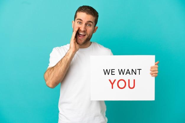 격리된 파란색 배경 위에 있는 잘생긴 금발 남자가 we want you 보드를 들고 소리를 지르고 있습니다.
