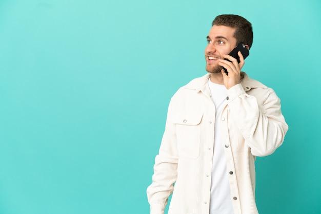 携帯電話との会話を維持している孤立した青い背景の上のハンサムなブロンドの男