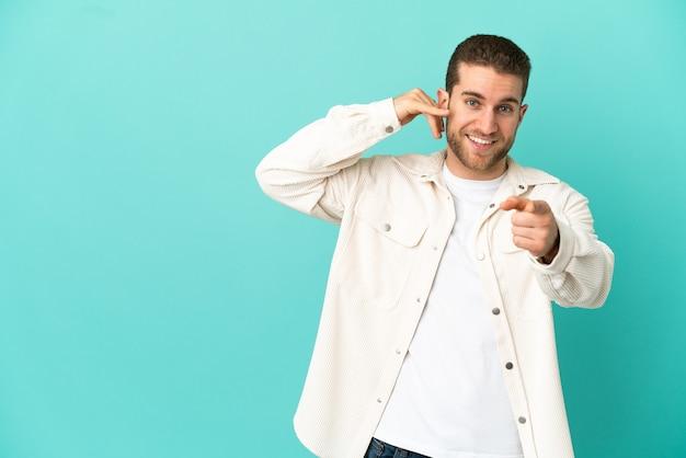 Красивый блондин на изолированном синем фоне, делая жест телефона и указывая вперед