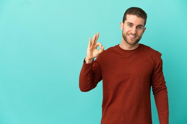 Красивый блондин на изолированном синем фоне, показывая пальцами знак ок
