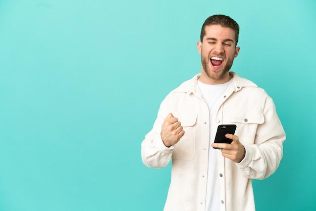 Красивый блондин на изолированном синем фоне с телефоном в позиции победы