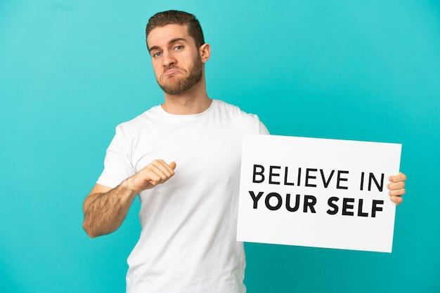 Красивый блондин над изолированной синей стеной держит плакат с текстом «верь в себя» с гордым жестом