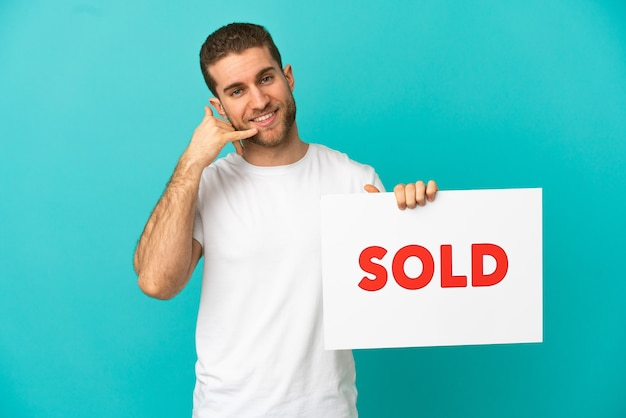 Красивый блондин над изолированной синей стеной держит плакат с текстом продано и делает приближающийся жест