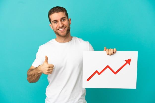 엄지 손가락으로 성장 통계 화살표 기호로 기호를 들고 고립 된 파란색 벽 위에 잘 생긴 금발 남자