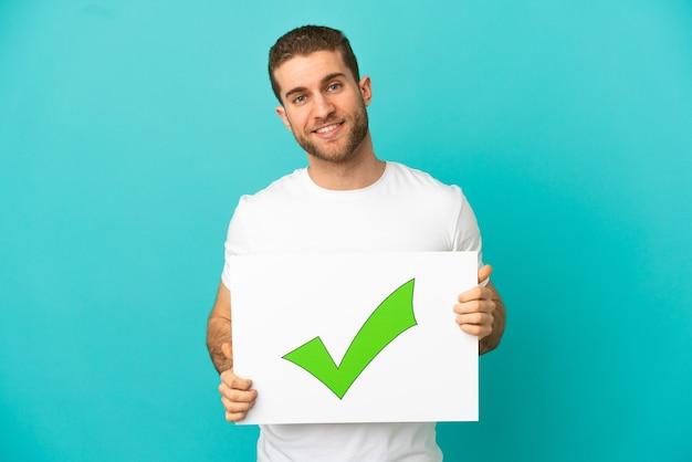 幸せな表情で緑のチェック マーク アイコン テキスト付きのプラカードを保持している孤立した上のハンサムな金髪の男