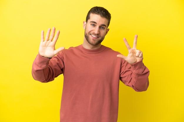 손가락으로 8 세 고립 된 노란색 배경 위에 잘 생긴 금발의 남자