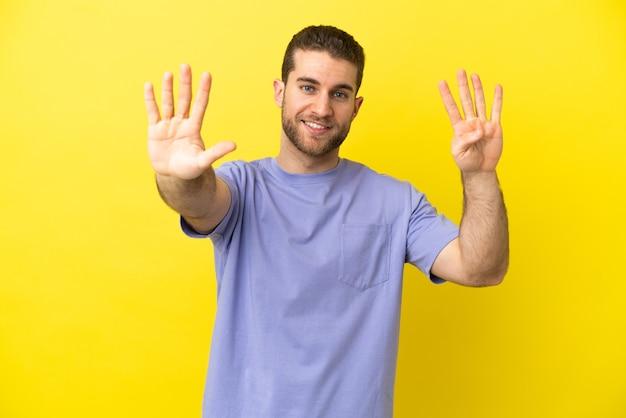Красивый блондин на изолированном желтом фоне, считая девять пальцами