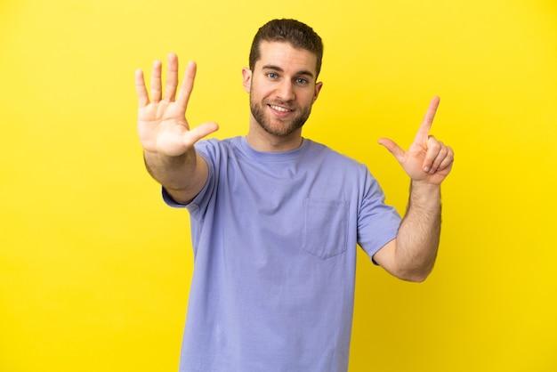 Красивый блондин на изолированном желтом фоне, считая семь пальцами