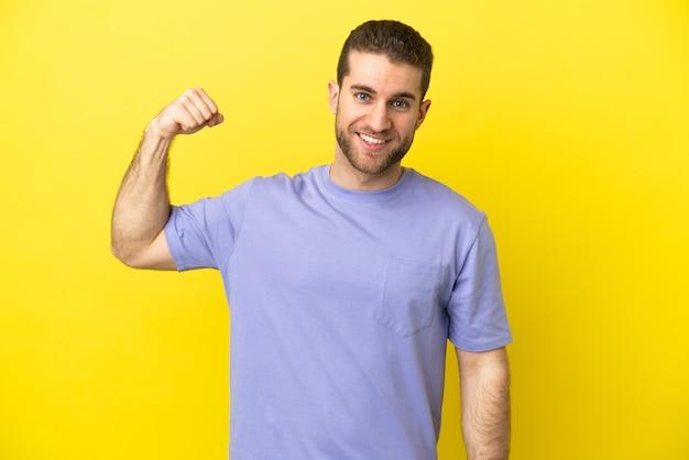 강한 제스처를 하 고 고립 된 노란색 배경 위에 잘 생긴 금발 남자