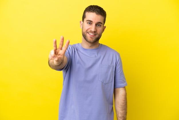 Красивый блондин на изолированном желтом фоне счастлив и считает три пальцами