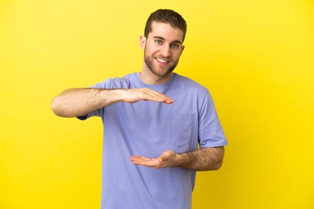 Красивый блондин на изолированном желтом фоне, держащий воображаемое пространство на ладони, чтобы вставить рекламу