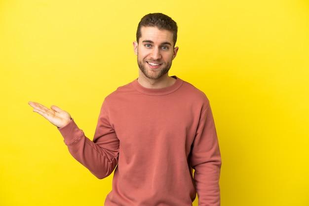 광고를 삽입하려면 손바닥에 상상 copyspace 들고 고립 된 노란색 배경 위에 잘 생긴 금발의 남자