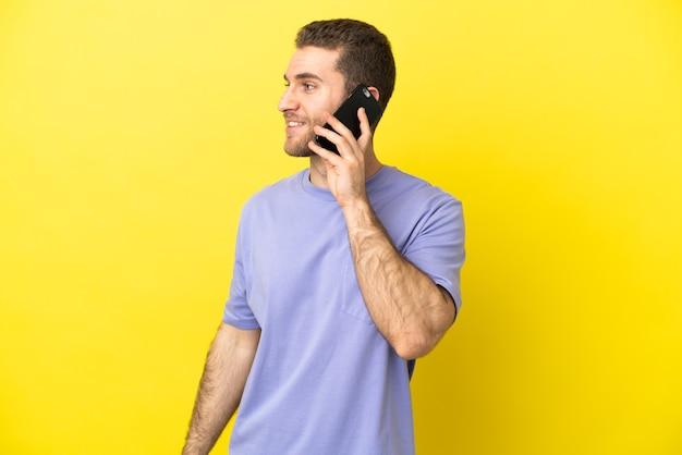誰かと携帯電話との会話を維持している孤立した黄色の背景の上のハンサムなブロンドの男