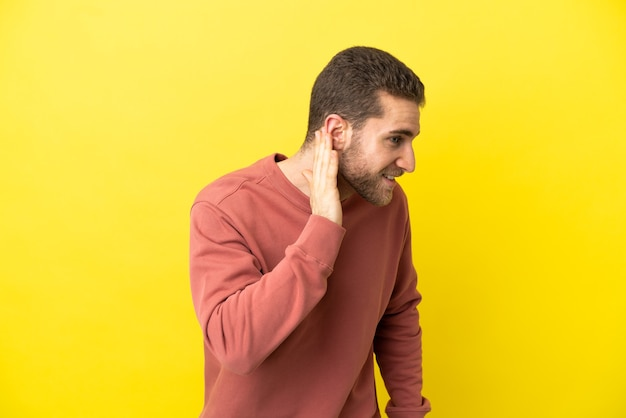 Красивый блондин на изолированном желтом фоне слушает что-то, положив руку на ухо