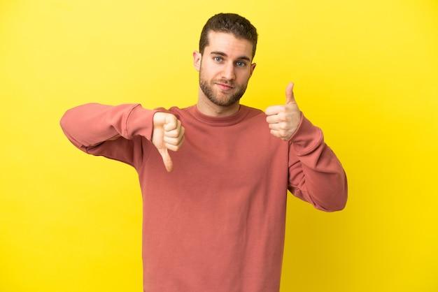 격리된 노란색 배경 위에 잘생긴 금발 남자가 좋은 징조를 만듭니다. 예, 아니요 미정