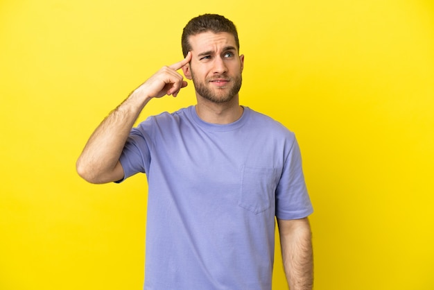 머리에 손가락을 넣어 광기의 제스처를 만드는 고립 된 노란색 배경 위에 잘 생긴 금발의 남자
