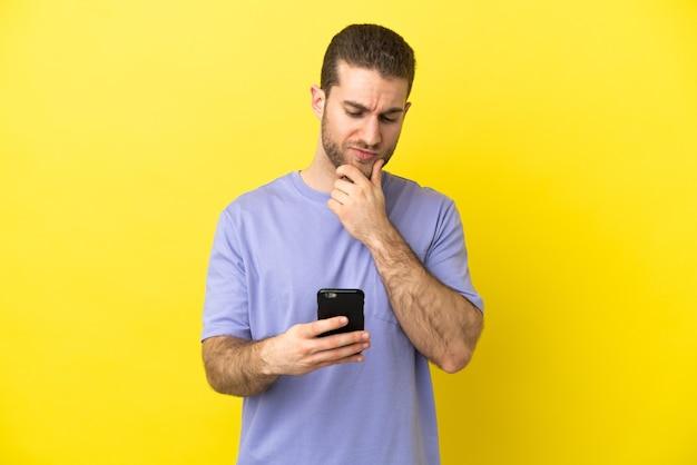 Красивый блондин на изолированном желтом фоне думает и отправляет сообщение