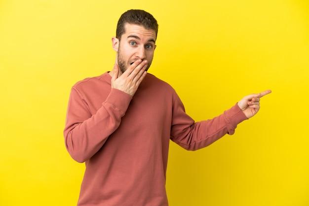 측면을 가리키는 동안 놀란 표정으로 고립 된 노란색 배경 위에 잘 생긴 금발 남자