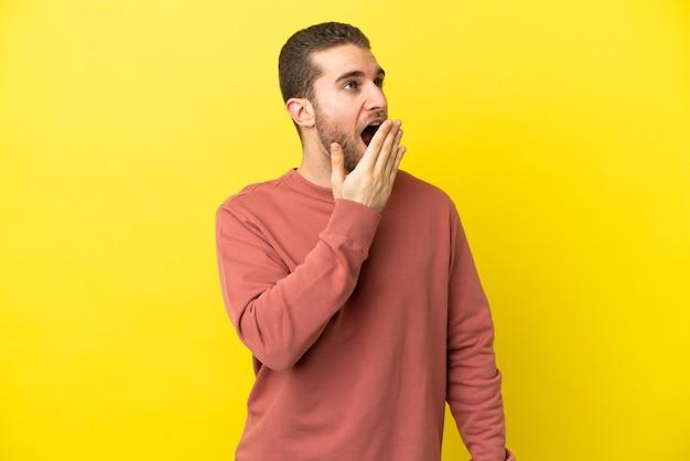 あくびと手で大きく開いた口を覆う孤立した黄色の背景の上のハンサムなブロンドの男