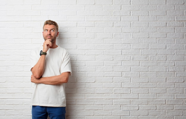 Handsome blonde man thinking against a grunge wall