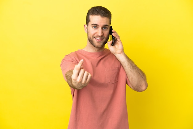 Handsome blonde man using mobile phone over isolated background doing coming gesture