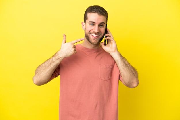Красивый блондин с помощью мобильного телефона изолировал фон, показывая большие пальцы руки вверх