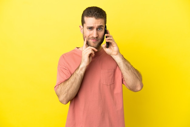 Handsome blonde man using mobile phone over isolated background having doubts while looking up