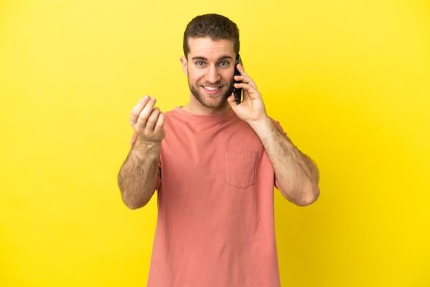 Красивый блондин с помощью мобильного телефона изолировал фон, делая денежный жест