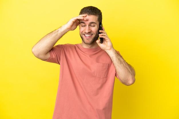 Красивый блондин с помощью мобильного телефона изолировал фон, много улыбаясь