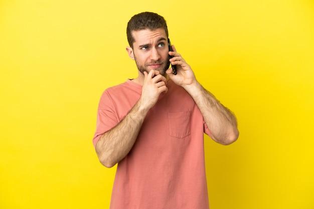 Красивый блондин с помощью мобильного телефона на изолированном фоне и смотрит вверх