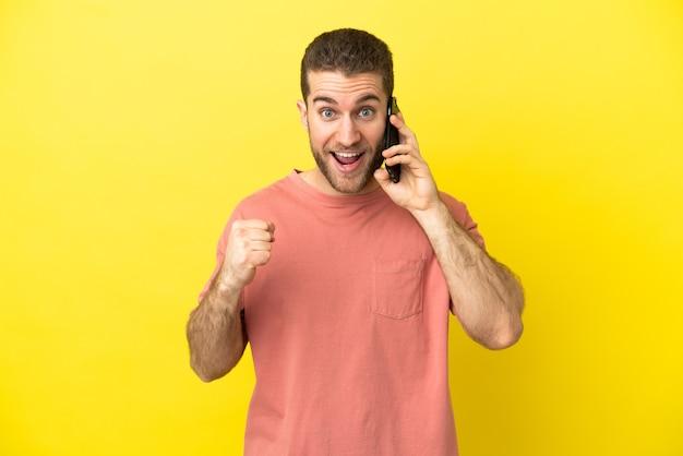 Красивый блондин, использующий мобильный телефон на изолированном фоне, празднует победу в позиции победителя