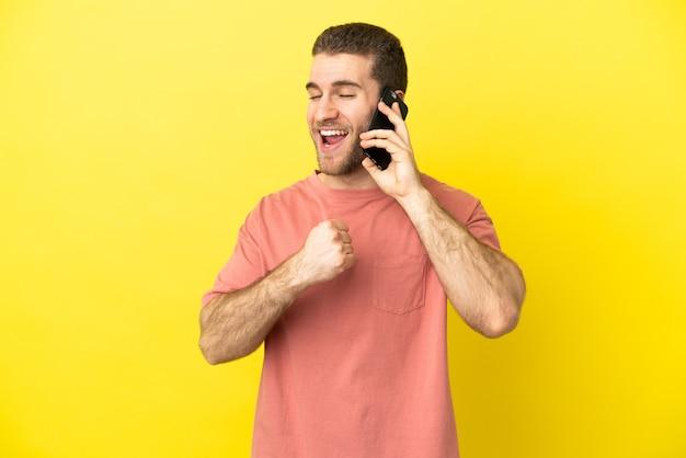 Красивый блондин с помощью мобильного телефона на изолированном фоне празднует победу