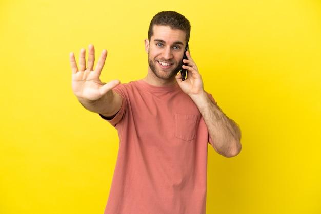 Красивый блондин с помощью мобильного телефона на изолированном фоне, считая пять пальцами