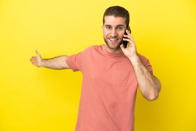 Красивый блондин, использующий мобильный телефон на изолированном фоне, протягивает руки в сторону, приглашая приехать