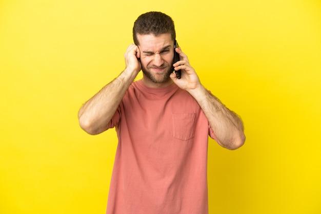 欲求不満と耳を覆っている孤立した背景の上に携帯電話を使用してハンサムなブロンドの男