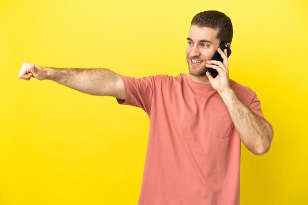 Красивый блондин с помощью мобильного телефона на изолированном фоне, показывая жест пальца вверх