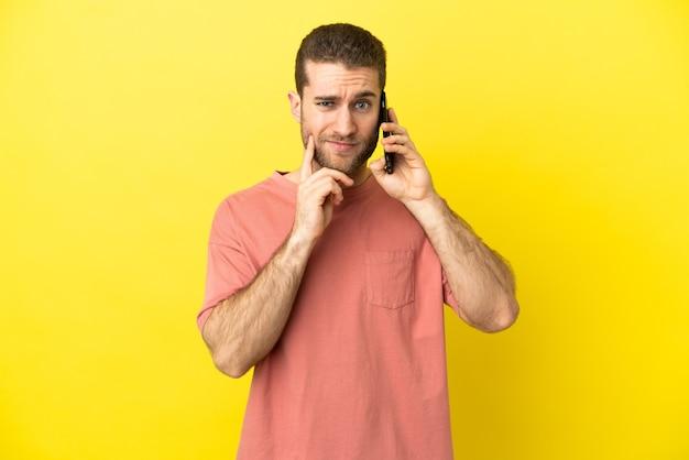 Красивый блондин с помощью мобильного телефона на изолированном фоне, сомневаясь, глядя вверх