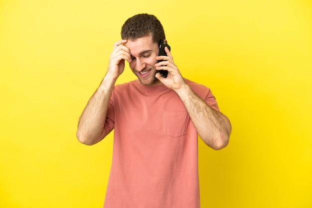 笑っている孤立した背景の上に携帯電話を使用してハンサムなブロンドの男