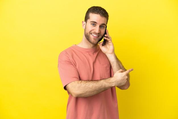 後ろ向きの孤立した背景の上に携帯電話を使用してハンサムなブロンドの男