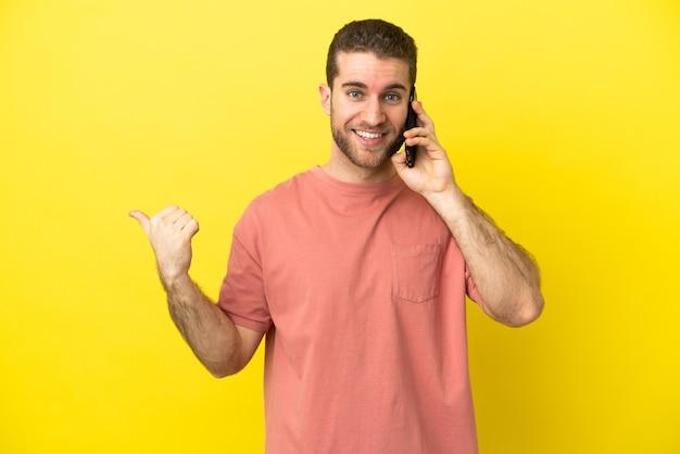 Красивый блондин с помощью мобильного телефона на изолированном фоне, указывая в сторону, чтобы представить продукт