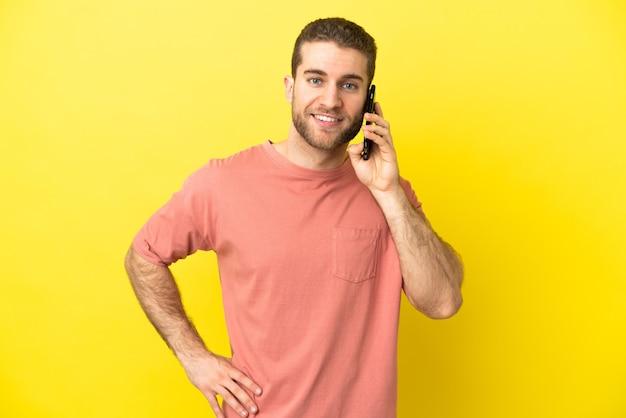 腰に腕と笑顔でポーズをとって孤立した背景に携帯電話を使用してハンサムなブロンドの男