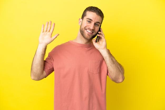 幸せな表情で手で敬礼する孤立した背景の上に携帯電話を使用してハンサムなブロンドの男