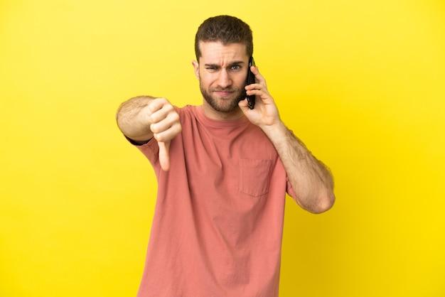 Красивый блондин, использующий мобильный телефон на изолированном фоне, показывает палец вниз с отрицательным выражением лица