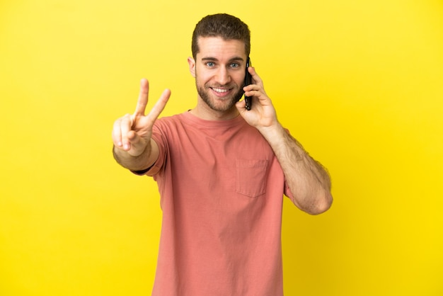 Красивый блондин с помощью мобильного телефона на изолированном фоне улыбается и показывает знак победы
