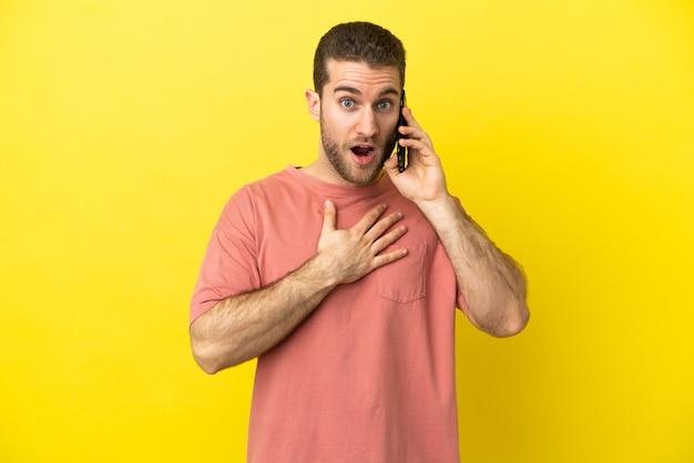 Красивый блондин, использующий мобильный телефон на изолированном фоне, удивлен и шокирован, глядя вправо