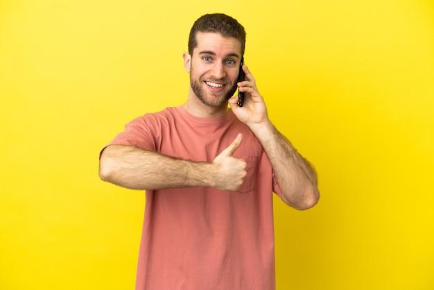 親指を立てるジェスチャーを与える孤立した壁の上に携帯電話を使用してハンサムなブロンドの男